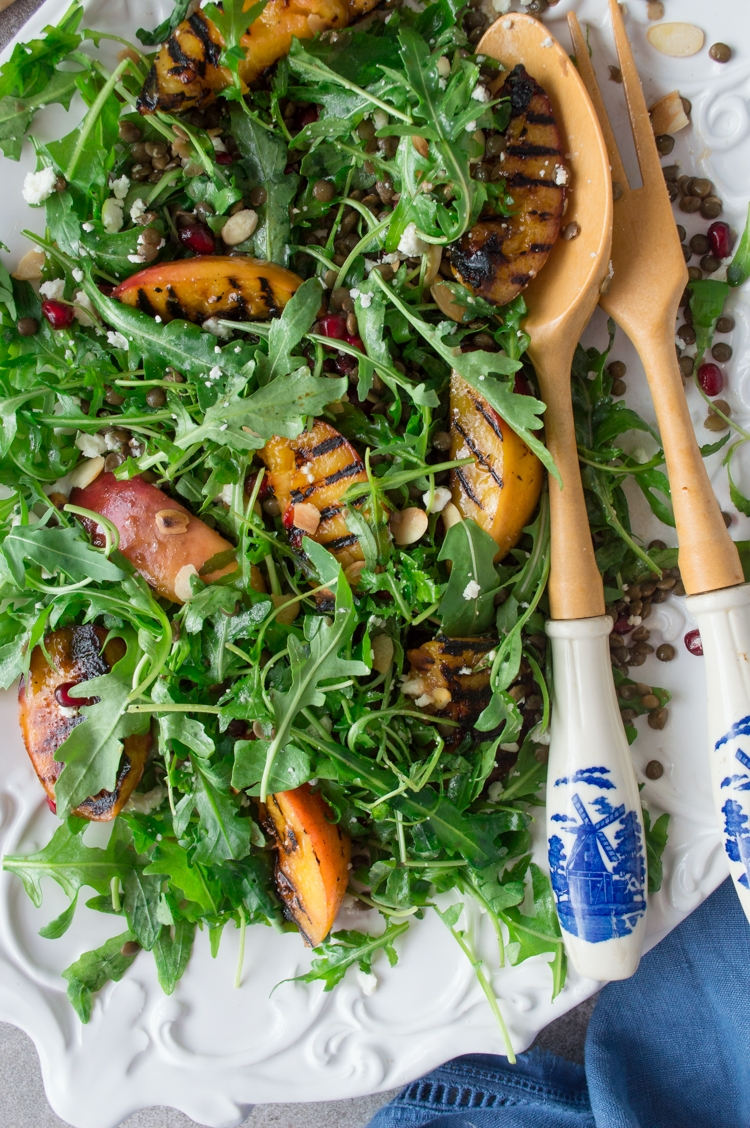 A white plate with grilled nectarines, arugula, lentils & salad serving spoons