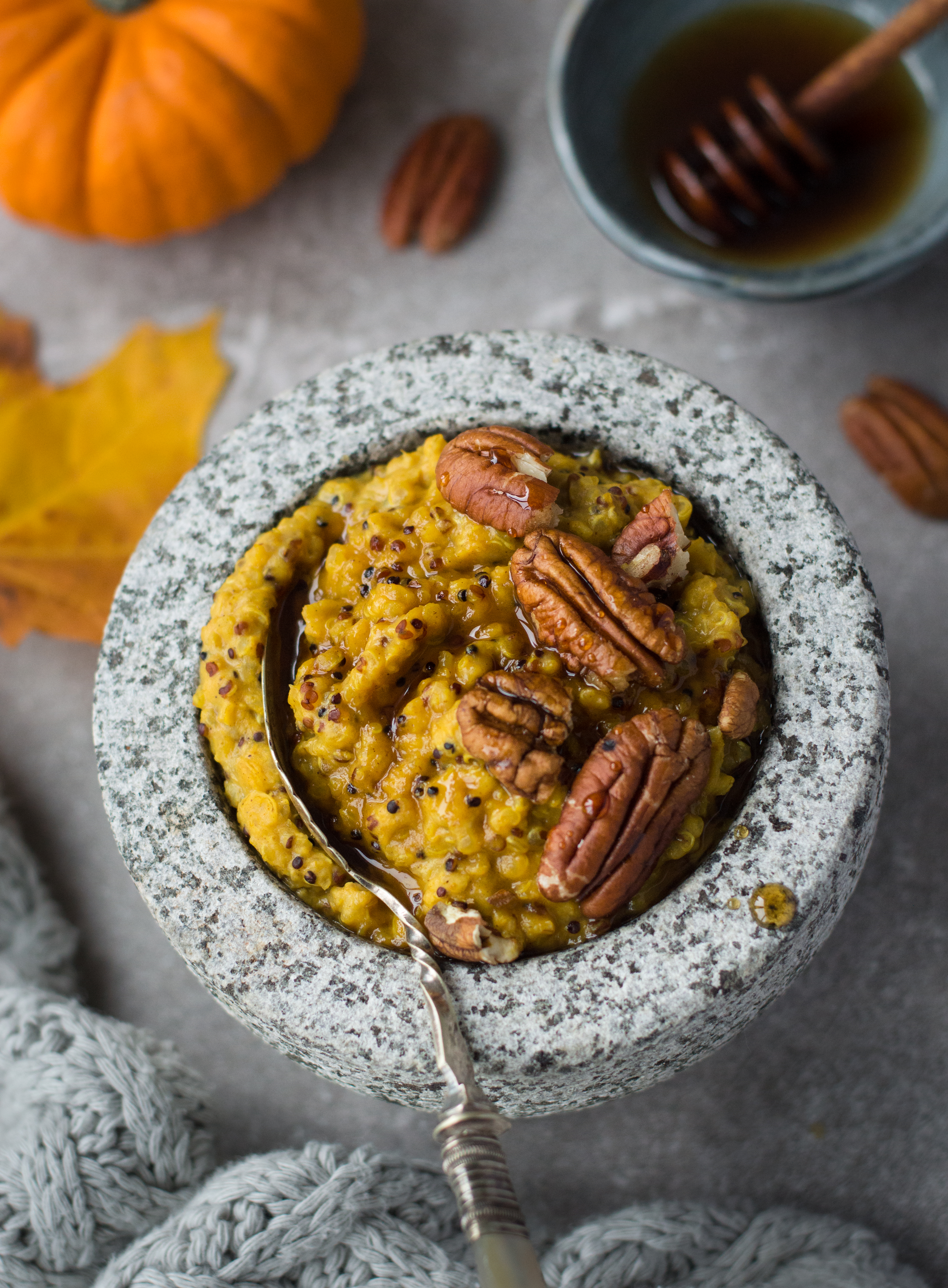 A bowl of pumpkin porridge with pecan nuts and maple syrup