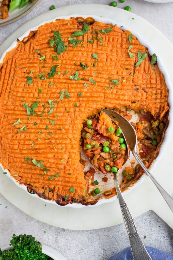 Vegan cottage pie & sweet potato mash in a round white dish